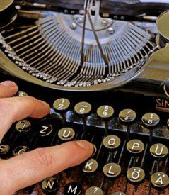 Eine Hand auf der Schreibmaschine, Symbolbild für das Impressum