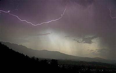 Gewitter vor Gebirge: ein Blitz als Symbol für ortsunabhängige Arbeit als freier Online Redakteur