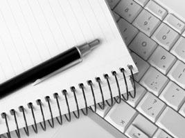 Schreibblock und Stift auf PC-Tastatur: Symbolbild für die Arbeit als freier Texter